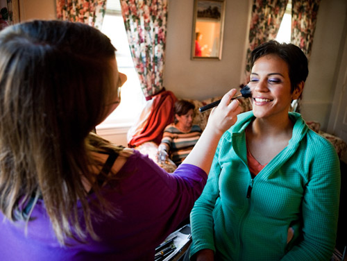 makeup artist applying blush to latina bride purple eyeshadow