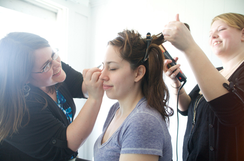 makeup artist and hairstylist working simultaneously on bride