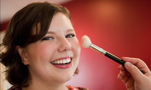 Bride with natural makeup smiling while blush is applied