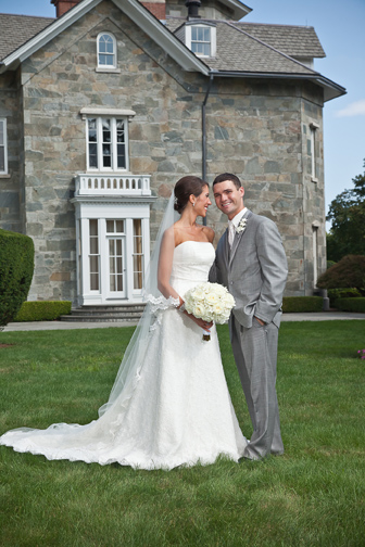 Elegant bride & groom posing in front of beautiful home