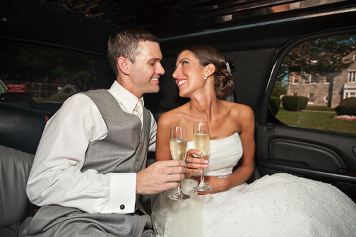 Bride & groom toast each other with champagne in the limo