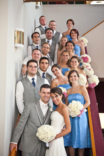 Bridal party posed on a staircase, wearing blues & greys