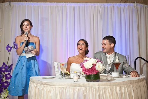Bride laughing in response to her sister's toast