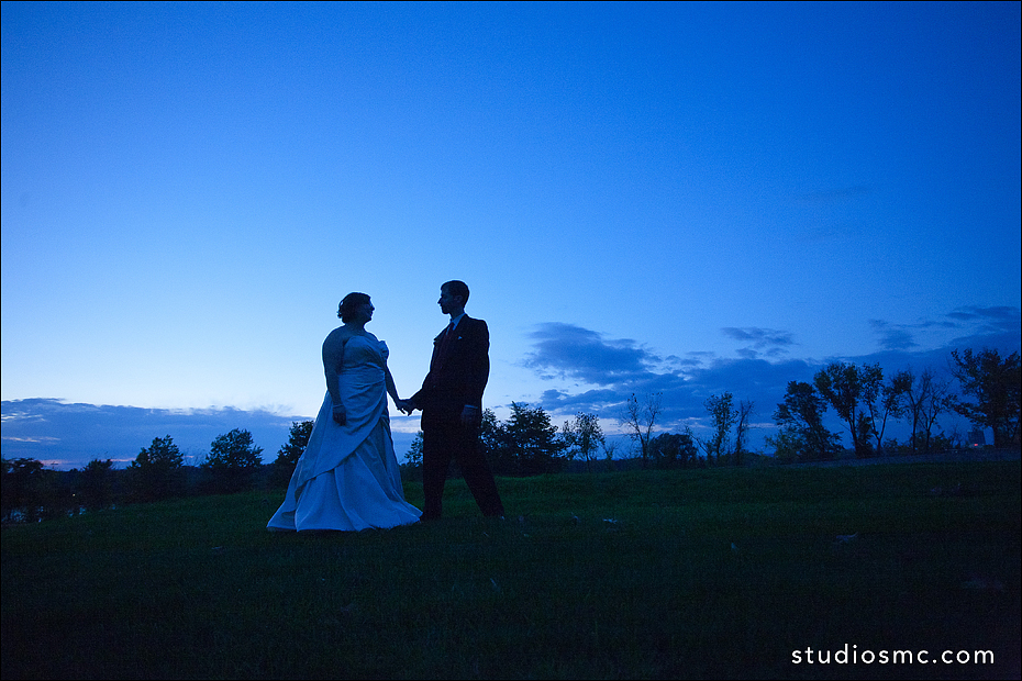 bride and groom outdoors at dusk holding hands