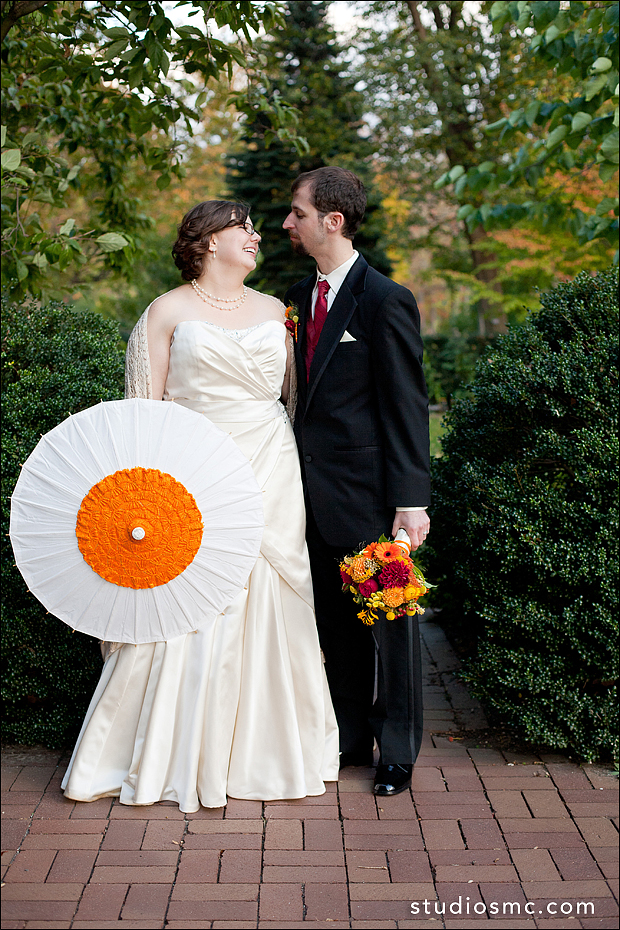 Bride holding hand embroidered orange parasol
