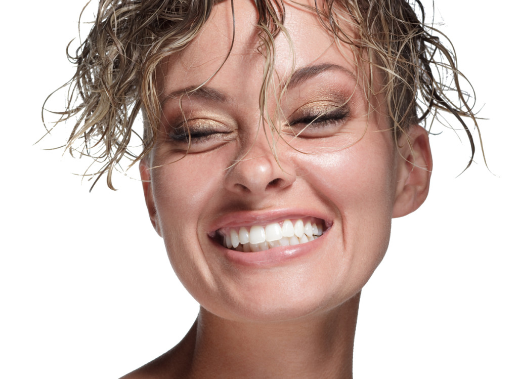 smiling model with wet hair and metallic gold and bronze eye makeup