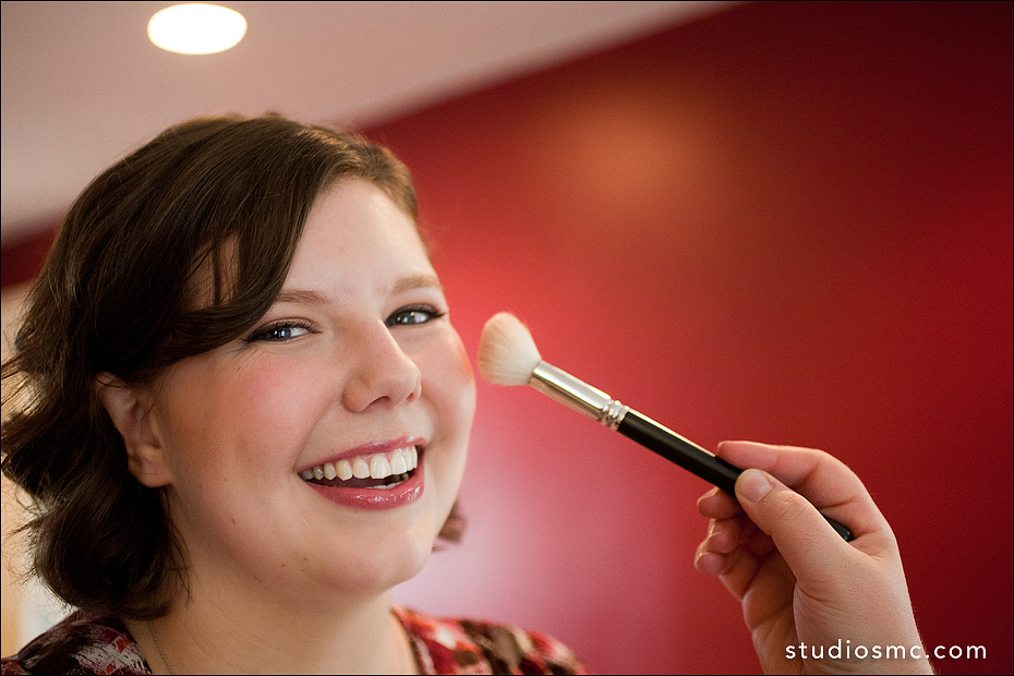 Bride with natural makeup and glossy lips smiling as blush is applied
