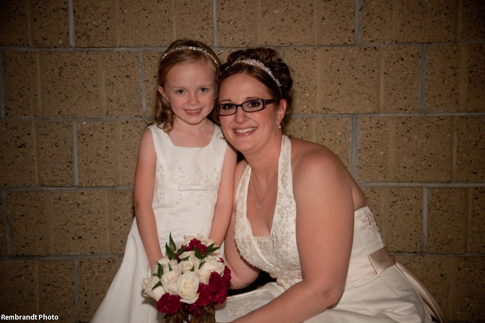 Bride wearing glasses posing with flower girl