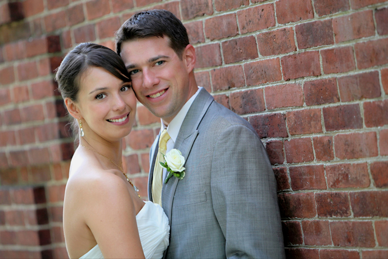 Elegant bride and groom posing by brick wall