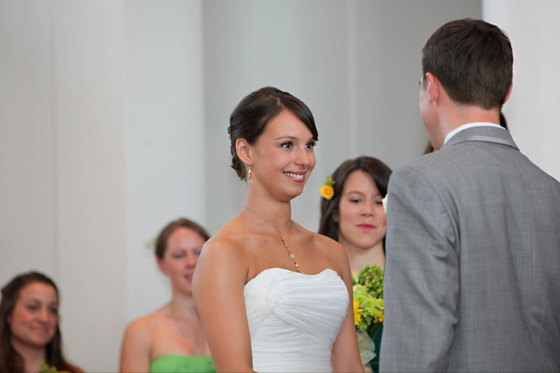 Bride with natural makeup smiling at groom during wedding ceremony