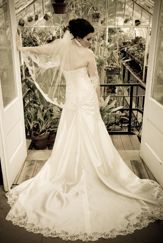 Bride standing before a greenhouse in her dress and veil