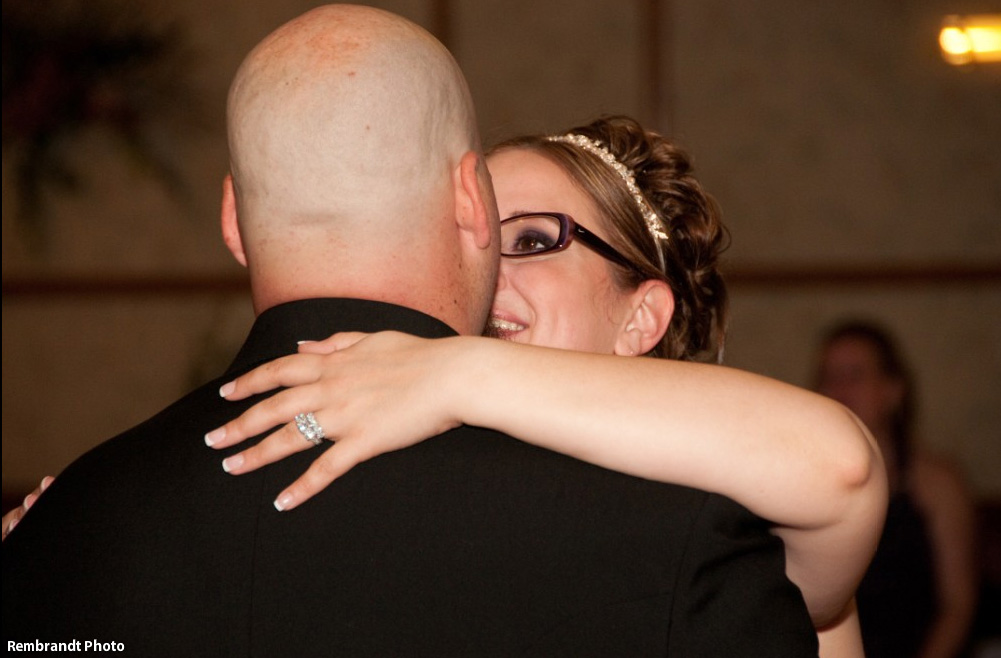 Bride with smoky eye makeup and glasses dancing with groom