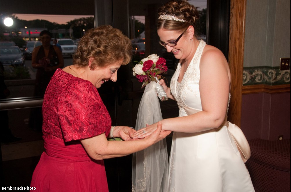 Bride showing her ring to a wedding guest