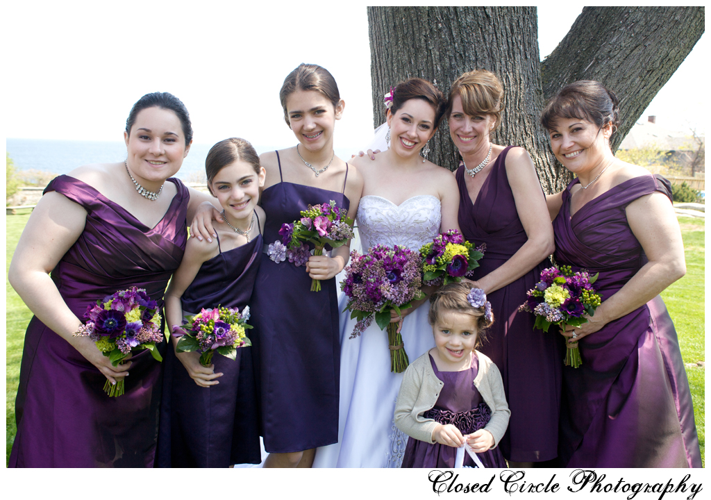 wedding party and flower girl in royal purple dresses matching flowers