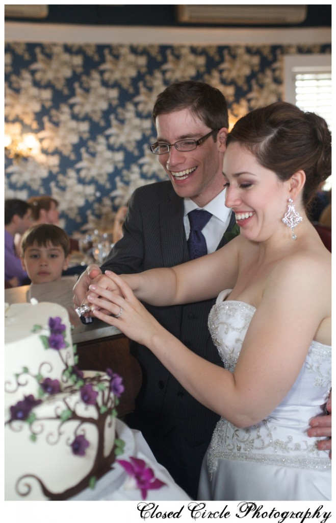 Bride and groom cutting cake decorated with branches and purple flowers