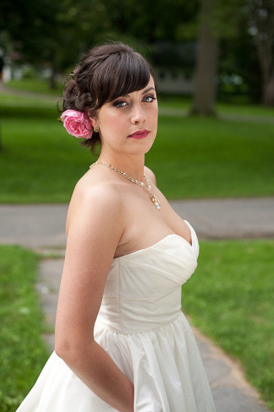 Vintage bride with pink lips, hair flower, and a pocketed wedding dress