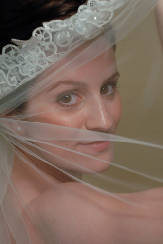 bride with natural dewy makeup peering through her veil