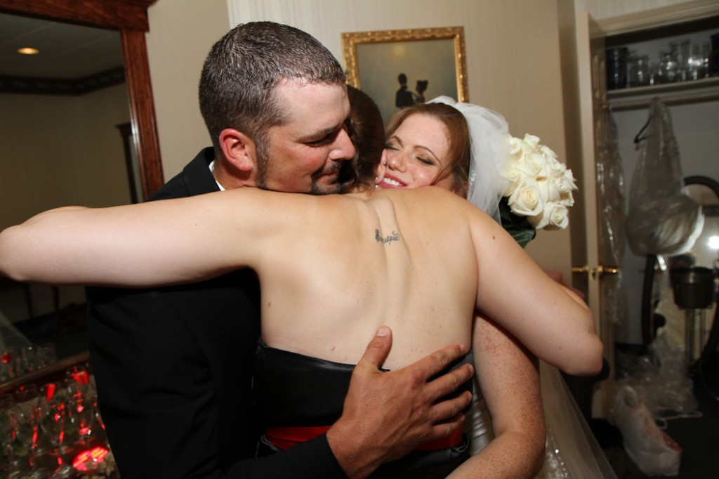 glowing brides gets a hug at a wedding