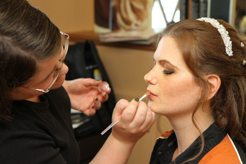 freckled bride getting lipstick applied by a pro makeup artist