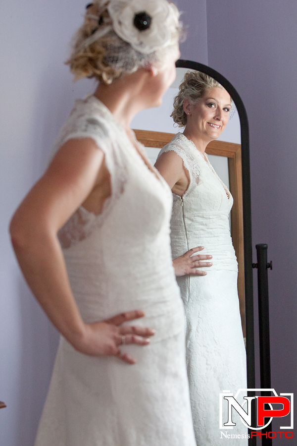 bride admiring her dress in the mirror