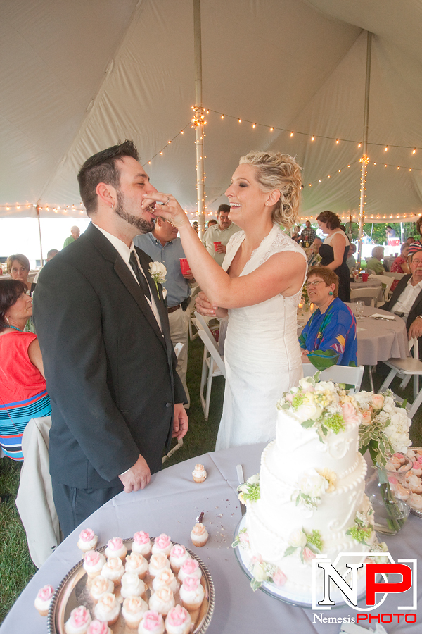 bride feeding cake to the groom at a backyard reception