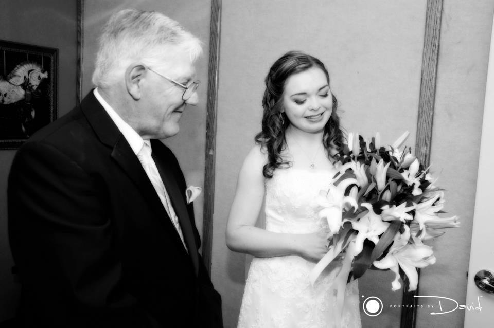 black and white photo of a pretty bride admiring her bouquet