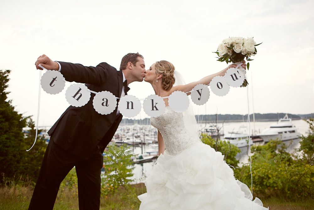 bride &amp; groom holding up thank you sign by the nh seacoast