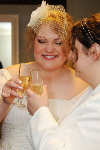 brides toast one another with champage