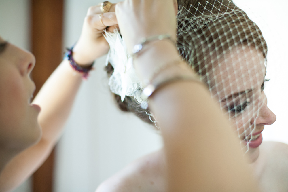 bride getting her birdcage veil applied