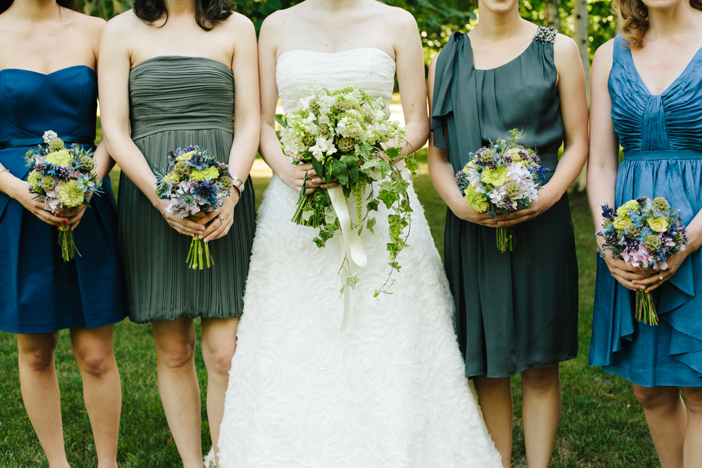bridal party wearing different dresses shades of blue and green