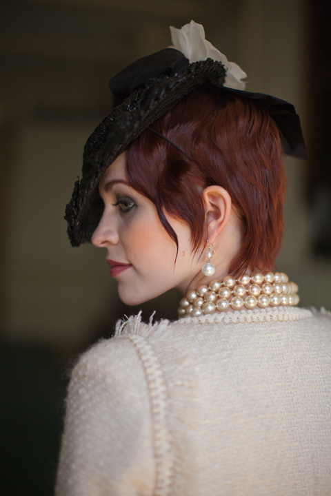 Elegant bride wearing pearls and a hat with rosy cheeks, smoky eyes and plum lips