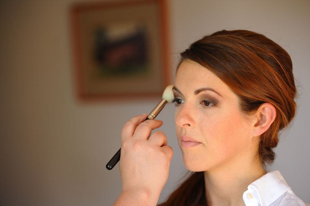 applying smoky eye makeup to a bride