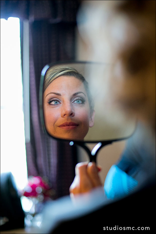 bride looking in the mirror at her makeup