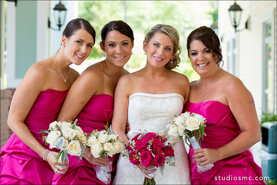Bride with fuchsia bouquet and bridesmaids in matching pink dresses