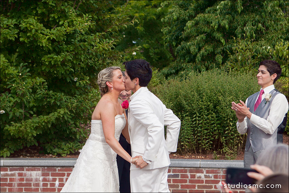 Two brides kiss at their wedding ceremony in Northampton MA