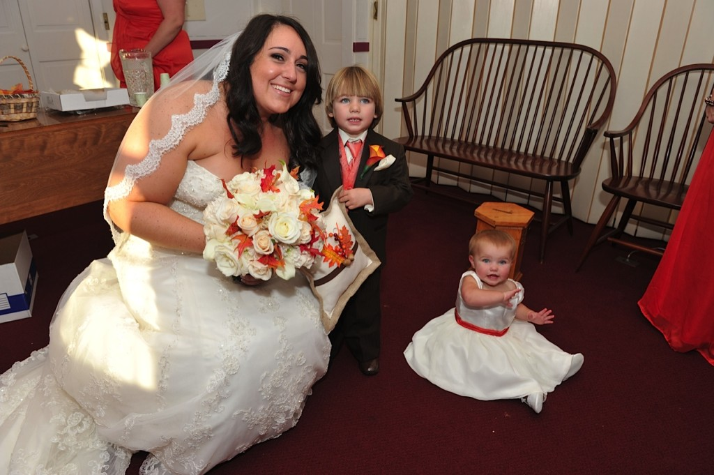 bride posing with her bouquet ring bearer and flower girl