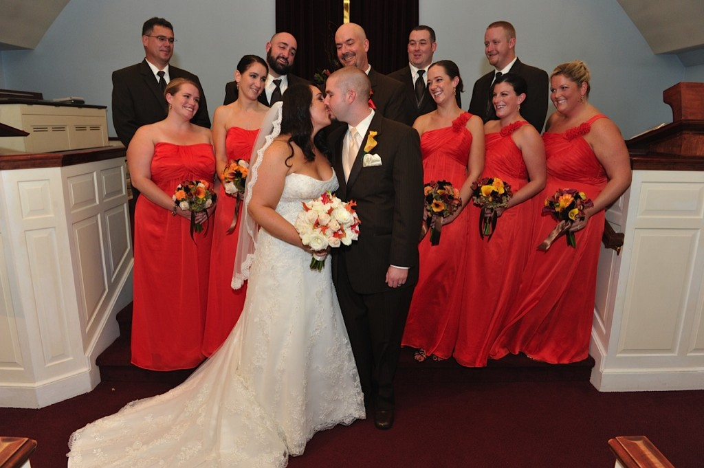 Bride kisses her husband orange bridesmaid dresses