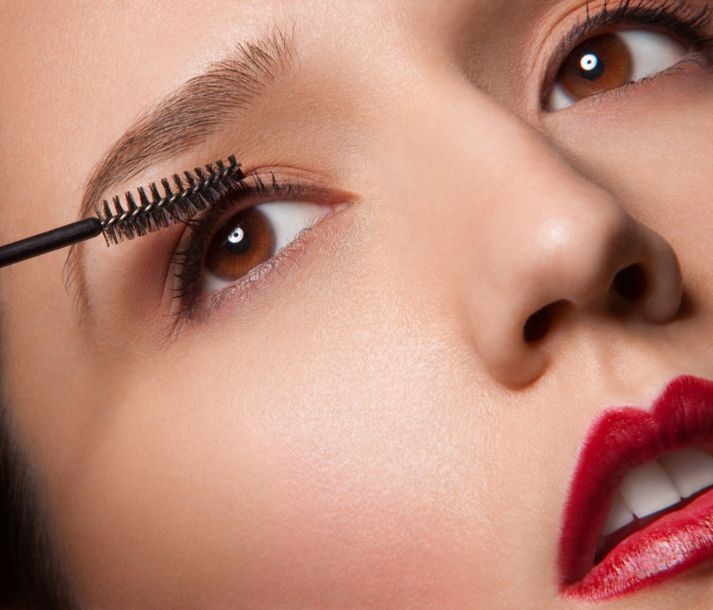 Model with red lips combing through eyelashes with clean mascara wand