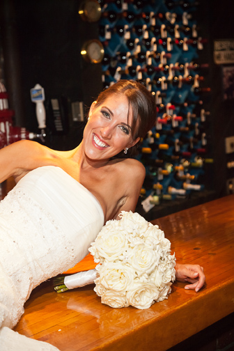 Elegant bride posing on a bar with her bouquet