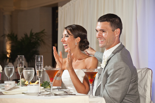 Bride laughing & clapping in response to a toast