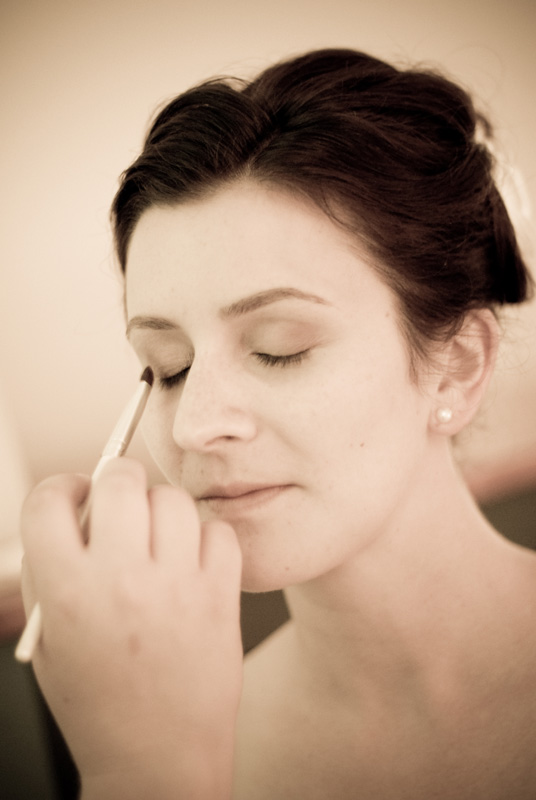 Bride getting eye makeup applied on her wedding day