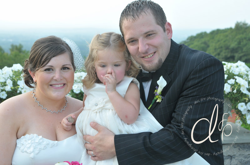 Bride and groom posing after ceremony with daughter