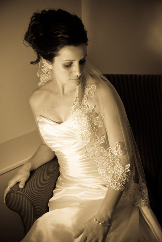B&W show of bride seated with veil draped over her arm