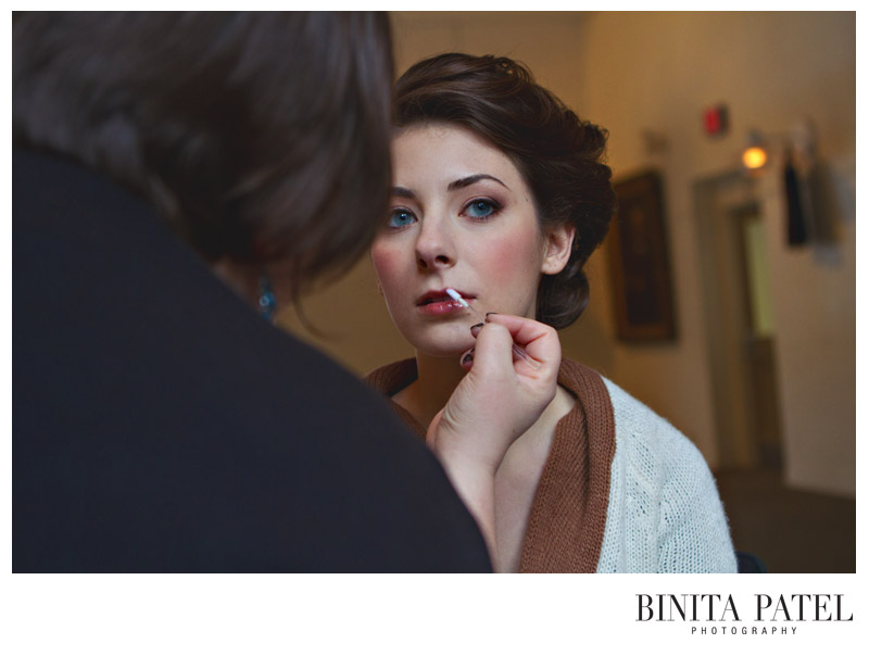 applying pink lipgloss to a beautiful bride