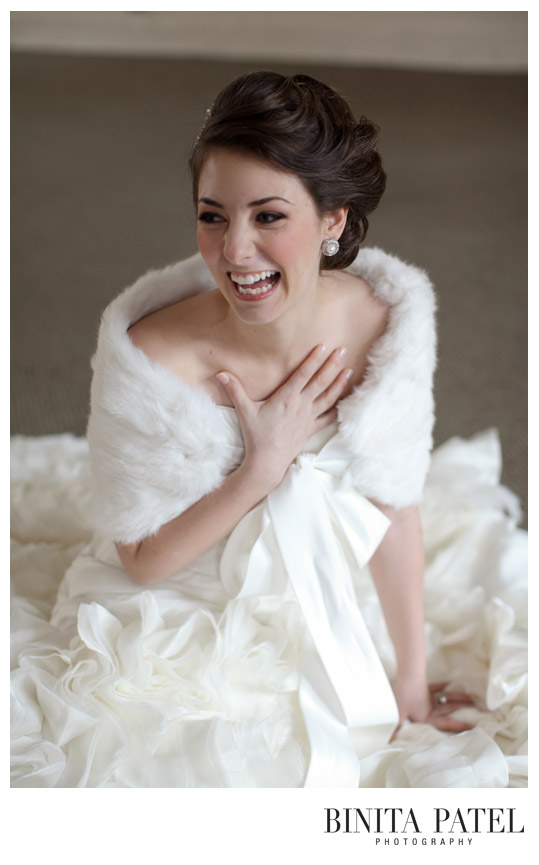 beautiful bride laughing while wearing a fur wrap