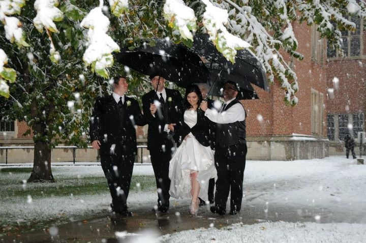 bride walking beneath an umbrella during a snowstorm