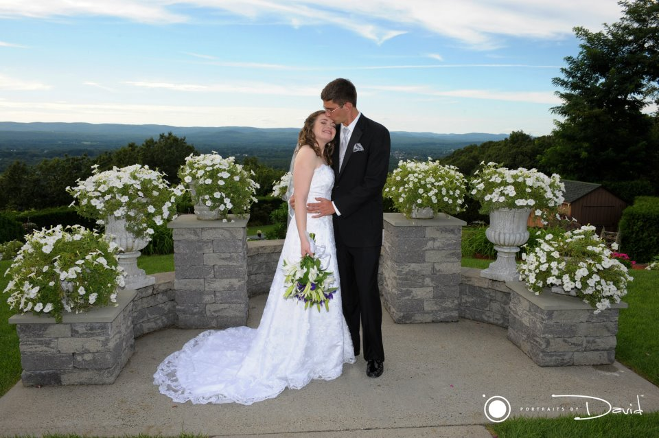 bride and groom posing in front of a nountain backdrop in holyoke ma