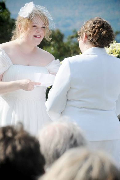 bride reads vows to her partner at their wedding ceremony