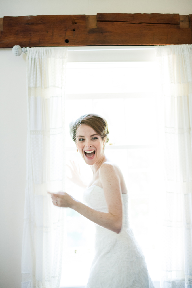 laughing bride peeking out a window
