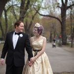 Bride and groom walking hand in hand on Comm Ave in Boston MA